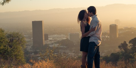 Boy and girl kiss at sunrise